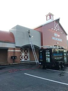 Curb Appeal owner on ladder in front of large commercial property building